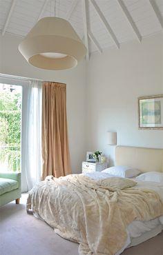 El respaldo de cama está tapizado en terciopelo y lienzo teñido por Ana Fuchs. Su delicado color manteca se repite también en el quillango de piel de nutria (Divino Cordero) que se arruga a sus pies, y en la mega lámpara de techo (Iluminación Agüero).