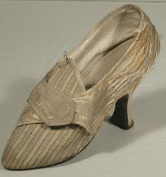Shoe, 1760-1770, England, Kid, Leather, Linen, Satin, Silk. Gold/champagne/silver striped ribbed silk with champagne satin latchets, and heel cover and brown leather soles. Lined with cream kid with a linen sock and lining to the vamp except for a small piece of green and white striped silk across the tongue. Decorated with champagne silk binding along the edges of uppers, latchets, back and side seams. Turnshoe construction. Snowshill Manor © National Trust / Richard Blakey