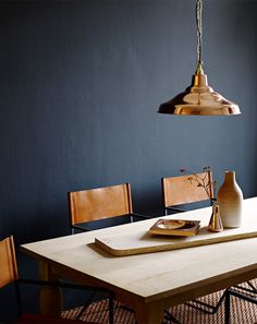 Dark wall, light wood table with black legs, lots of light from windows, leather chairbacks, Turkish rug