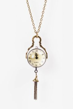 Brass colored clock necklace with a tassle. The other side of the ball features the innerworkings of the clock.