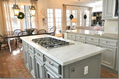 Carrara, or it could be Statuary, marble on the island in this kitchen. mix of the marble with countertops made of concrete. I love the gray cabinets and the two lanterns over the table.