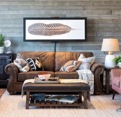 Boho style living room. Great rustic plank wall, brown sofa, bench used as ottoman, pops of color. Love the feather art!