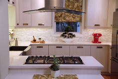 We created a regal kitchen space with plenty of cabinet space, state-of-the-art appliances, a stunning glass range hood, lots of spaces to store wine…and did we mention the glowing onyx backsplash?  Oh yeah, there's that too!  Designed and built by Paul Lafrance Design.