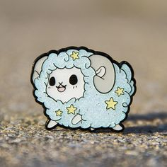 "Our brand new enamel pin for Solram! He's 1.75"" wide and has a double pin back. He's also infused with glitter in his wool!"