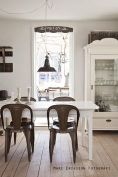 Metal chairs and vintage storage cabinet in a white dining area