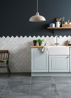 White metro kitchen tiles used as herringbone tiles against a navy wall with powder blue kitchen cupboards from RedOnline: