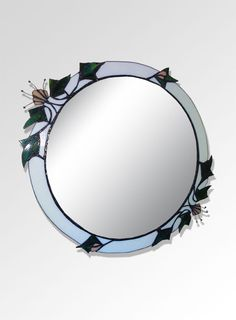 This round mirror features delicate peach flowers with wire embellishments, surrounded by contrasting spiky ivy leaves. The colours were chosen to complement the decor in the client's home.