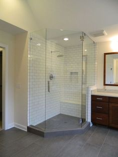 Gray tile flooring with subway tile shower walls and bench. Shower niche above built-in bench, Frameless walk-in glass shower enclosure. Stained cabinetry with decorative hardware and granite countertops. Custom mirror molding.