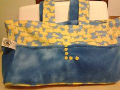 Cute ducks on cotton fabric are paired with soft blue flannel. The duck button were shaped into an L for the name of the child whose parents received this bag.