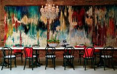 Gorgeous exposed brick wall, oversized abstract art, Bentwood chairs and cafe style dining table with a glamorous chandelier.