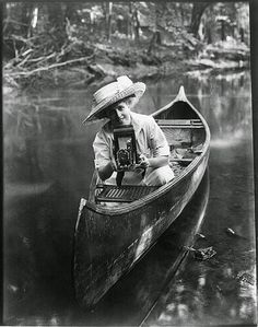 vintage everyday: Woman in canoe pointing camera, c.1909