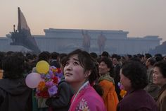 A woman looks up at the end of a opening ceremony for a statue unveiling at Mansu Hill in April 2012. The sky was smoke-filled after fireworks were lit. PHOTOGRAPH BY DAVID GUTTENFELDER, AP