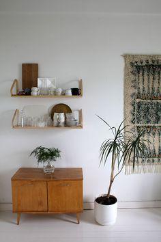 Un intérieur bohème minimaliste avec un meuble bas vintage, une plante et un tissage au mur