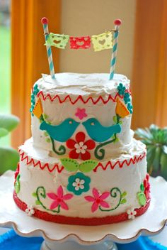 Mexican Folk Art Cake Fondant decorations on a vanilla buttercream cake filled with our own local raspberry preserves.