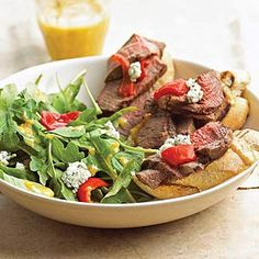 Grilled Steak Bruschetta Salad. This colorful salad is almost too pretty to eat. Arugula, grilled bread, steak, blue cheese, and sweet peppers make a dazzling main-dish presentation for dinner.