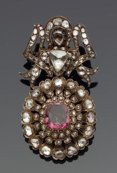 An impressive Qajar diamond and ruby-set gold Brooch   Persia, 19th Century  composed of two hinged openwork sections, one in the form of an oval tiered rosette set with a large central spinel within concentric layers of diamonds forming petals, the upper section in the form of a split palmette, set with a large pear-shaped diamond at the intersection and smaller stones