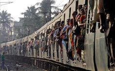 The world's busiest and third-largest rail network carries 23 million travellers every day along the nation's 65,000 kilometres of track.  Commuters travel in a packed local train in Calcutta