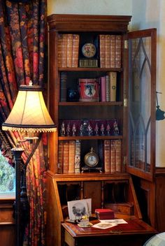 Secretary with perfect reading lamp and chintz drapes.