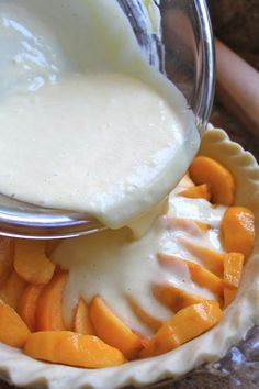 Pouring custard into peaches in pie crust.