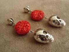 Brinco com pingente de caveira em metal prata e resina indiana com motivo floral na cor vermelha. R$32,00