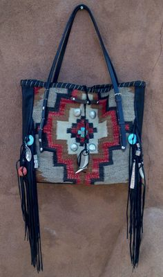 Navajo blankets / rugs, vintage or gently-used horse tack, and deer, elk or cowhide leathers. I embellish the bags with vintage trade beads, turquoise, coral, nickel silver/German silver Concho buttons, nickel silver spots/studs, and deer antler tips.