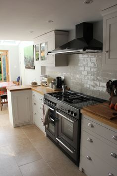 "Rangemaster Toledo 110 in gunmetal with the matching hood. Tiles from Topps Tiles ""chic"" range. Apparently they are exactly the same as some at Fired Earth. Come in shades of grey/white in crackled glaze. The one we thought we ordered was bright white ""Chic Blanco"" but alas....they were up before I could correct the error. Nice enough though."