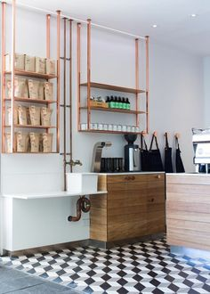 Cubic tiled floor - love the sink area with exposed copper piping, and the copper shelving units /