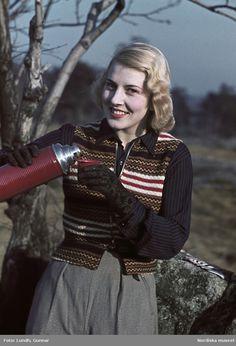 1943. Kvinna i randig, virkad väst, blå blus och svarta handskar häller ur en termos. Fotograf: Gunnar Lundh