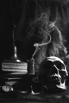 the coolest part of this photo is the way the smoke takes in the light to show its formation and the way it dances in the air away from the candle. the dark crevasses in the skull are unidentifiable on the completely dark left side but leave a scary character on the right side which is being hit by the downward angled light from the right side.-k