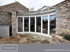 The complex shape of this characterful cottage was made possible by using this unique 6-door curved folding sliding door system in Accoya