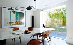 A London home with modern art at its centre -contemporary dining room, large scale art, large custom marble table, light by Serge Mouille, all looking out to garden