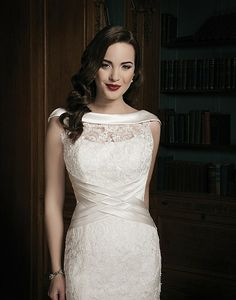 A regal satin rolled collar accents this lace illusion Sabrina neckline on this lace fit and flare wedding dress