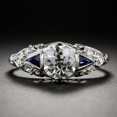1.05 Carat Art Deco Engagement Ring,  A beautiful bright-white and shining European-cut diamond, weighing 1.05 carats, sparkles mightily from atop an elegantly tailored Art Deco engagement ring, handcrafted in platinum and tastefully adorned with glittering diamond-set shoulders, calibre sapphire epaulets, a fanciful filigree gallery and a hand engraved upper ring shank. This truly stunning and timeless vintage treasure dates from the 1920s-1930s.