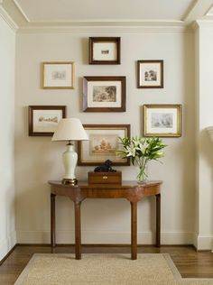 There's something about this--the arrangement? the wooden frames complementing the wood of the console? the white walls?--that makes this entryway just perfect.