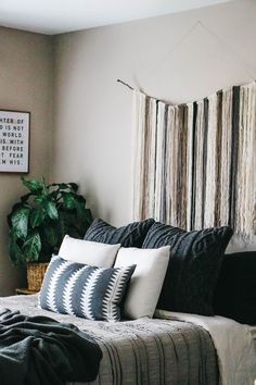 This earthy boho bedroom is complete with yarn art, house plants, layered pillows, and a gallery wall. Read on for tips on creating an atmosphere you love. @kilzbrand #sponsored