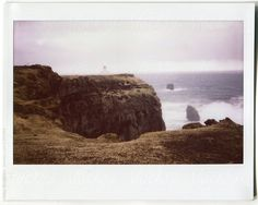Instax shot of Lighthouse on the rocky cliff by Nikolay Bondarev for Stocksy United