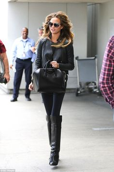 Flying solo: Chrissy arrived at LAX airport later on in skintight leggings and over-the-knee boots