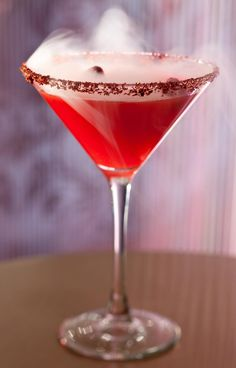 So fun! The Fire Breathing Dragon from The Cosmopolitan Las Vegas' Chandelier Bar  1/2 oz lemon juice 1 oz thai chili syrup 1/2 oz lemongrass syrup 1 oz raspberry puree 2 oz Bacardi dragonberry.  Assemble all ingredients and shake. Pour into a 10 oz pink peppercorn rimmed martini soiree with a spoon of 2 nitrogen charged smoking raspberries.