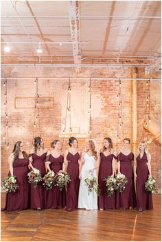 bride walks with bridesmaids in burgundy gowns | Planning a romantic winter wedding? Find inspiration from this Industrial December wedding at Art Factory Studios photographed by NJ Wedding photographer Idalia Photography. #IdaliaPhotography #ArtFactoryStudios #DecemberWedding #WinterWedding #IndustrialWedding