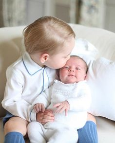 Prince George kisses his sister Princess Charlotte of Cambridge during their official photographs at Anmer Hall in mid-May in Norfolk, England.