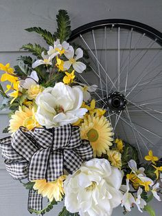 This unique Bicycle Wheel wreath is the perfect all-season accent for your home! A 17 black bicycle wheel serves as the base of this one-of-a-kind wreath. It is decorated with greenery, white magnolias, yellow daisies, small yellow roses, other faux florals, and features a black Wreath Crafts, Diy Wreath, Mesh Wreaths, Diy Crafts, Bicycle Wheel, Bicycle Rims, Yellow Daisies, A 17, Summer Wreath
