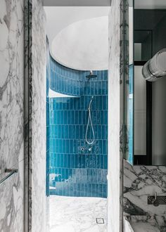 'Denim' tiles from Surface Gallery are laid vertically in the circular shower. Vanity is in Arabescato marble. | Story: Belle