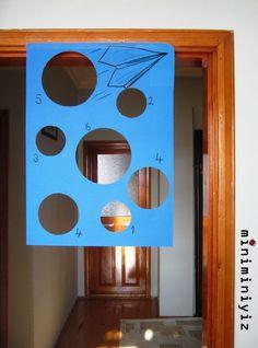 Kemerleri bağlayın bu oyunla fena uçacağız. :) Çocuklarla origami uçak yapıldıktan sonra hareketli bir uçmaca kaçmaca oyunu oynayalım. İsterseniz iki fon kartonunu birleştirerek de yapabileceğiniz bu düzenekle çocuklara aslında oyun görünümlü matematik yaptıracağız. Kesilmiş dairelerin içinden uçağını geçiren miniğimiz dairenin yanındaki sayıyı tanıyıp size söyleyecek ya da biraz ileri seviye …