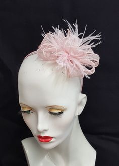 I have used a lovely pale baby pink sinamay for this fascinator which has hand rolled edge loops, with toning feathers. Mounted on a ribbon covered headband and primarily designed to be worn to the left side of the head, although it looks good to the right also. Handmade in the UK and ready to ship