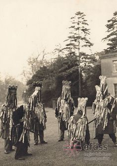 """North Waltham Mummers, Hampshire, c. 1949 (Photographer: Douglas Dickins) Mummers' Plays are a form of traditional drama, usually performed in the streets with a small but varied cast including St. George, the Turk, a doctor, and sometimes Santa Claus. Most mummers' plays feature a combat scene in which a combatant is wounded or killed and then miraculously revived by the doctor. The costume varies from region to region, but those in Hampshire are known for their """"tattered"""" jackets."""