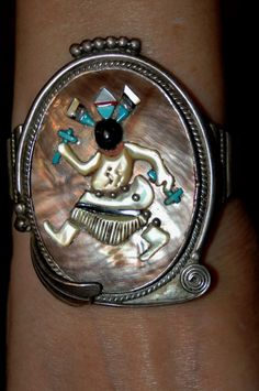 Heres another super fine vintage Zuni bracelet by Augustine & Rosalie Pinto.. This design is of the Zuni Apache Dancer and is considered rare and valuable. This same bracelet with a matching pendant is priced on Mudhead Gallery Item #BRZSMADARP1 for $5400.00 so buy this beautiful bracelet while you can! There are fabulous details in this stunning collectible bracelet! The face and dancer are made from a soft purple shell, turquoise, onyx, mother of pearl, coral and spiney oyster. I love the…