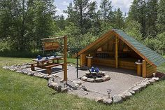 Exterior, horizontal, campfire area with shelter and picnic table, Golden Eagle Log Homes