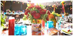 Pretty table setting - blue vintage jars, colorful table runner, tin cans as flower vases