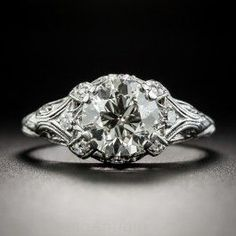 A European-cut diamond, weighing 1.84 carats, beams bright and beautiful from within a refined Art Deco mounting, die-struck and hand-finished in platinum, circa 1920s-30s. The scintillating stone, accompanied by a GIA Diamond Grading Report stating: M color - VS2 clarity, is embellished all around with a dozen tiny single-cut diamonds, hand-engraved details and delicate milgraining for a chic, sophisticated and sparkling effect. This original Jazz Age jewel is currently ring size 8.