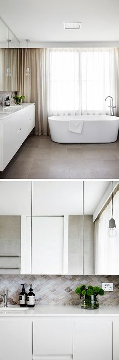In this modern ensuite bathroom, a large window adds plenty of natural light and the mirror helps to bounce that light around the room. A tile backsplash in natural colors compliments the curtains and flooring.
